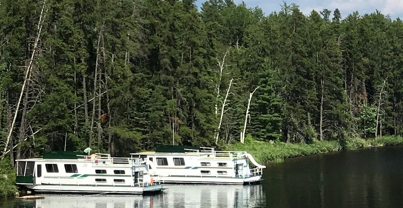 Two houseboats parked by the tree-lined shore